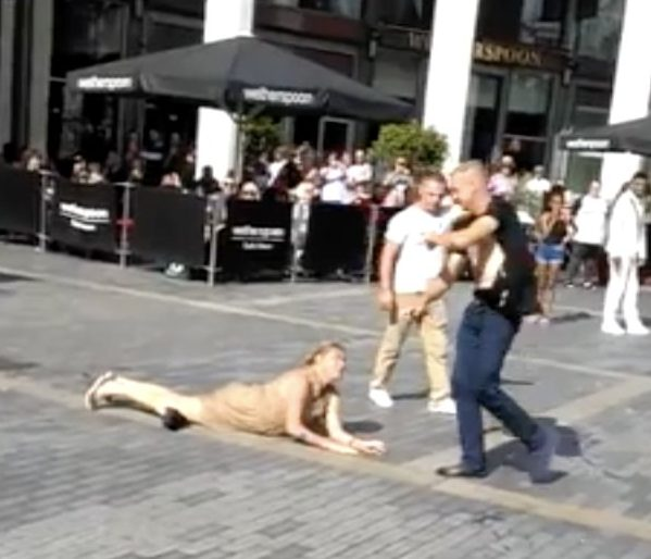 A woman is seen lying face down outside a Wetherspoons pub in Centenary Square, Bradford after an argument with the man in the ripped black t-shirt, Saturday August 4th, 2018. SHOCKING footage shows a WWE style brawl between three women and one man outside a Wetherspoons pub in Bradford, Yorkshire. In the astonishing clip, a crowd of cheering onlookers watch as the women wrestle on the ground and slap each other over the head with their FLIP-FLOPS. During the booze-filled brawl, a man?s t-shirt is completely ripped to shreds as passers-desperately try to break up the violent fight. It is believed that the incident took place on Saturday 4th August in Centenary Square in Bradford city centre. The outrageous three-minute clip ? which is filmed on a mobile phone ? begins with the sight of a woman in a beige dress lying face down on the pavement outside a Wetherspoons pub. ... SEE COPY ... PIC BY NEWS DOG MEDIA ... 0121 517 0019