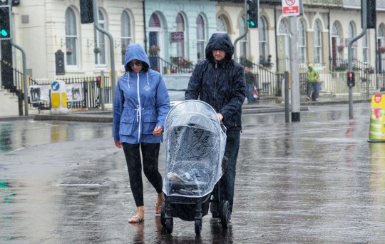 Mandatory Credit: Photo by Tom Corban/REX/Shutterstock (9787626b) Visitors make the best of a wet and windy Weymouth as the heatwave comes to an end and the South West gets some rain. Seasonal Weather, Weymouth, Dorset, UK- 11 August 2018