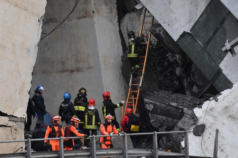epa06948876 Rescuers at the site of the collapsed bridge in Genoa, Italy, 14 August 2018. A large section of the Morandi viaduct upon which the A10 motorway runs collapsed in Genoa on Tuesday. Both sides of the highway fell. Around 10 vehicles are involved in the collapse, rescue sources said Tuesday. The viaduct gave way amid torrential rain. The viaduct runs over shopping centres, factories, some homes, the Genoa-Milan railway line and the Polcevera river. EPA/LUCA ZENNARO