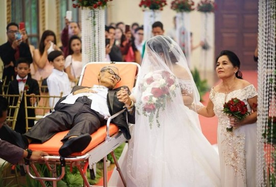 """Pic shows: Mr. Pedro Villarin walked his daughter down the aisle. This is the heartbreaking moment a dying father 'walked' his daughter down the aisle for her wedding while lying on a stretcher. Pedro Villarin, 65, was suffering from terminal liver cancer but it was his last wish to walk his daughter Charlotte Villarin down the aisle for her wedding. So the family hired an ambulance and a pirvate nurse to take him to the ceremony in the city of Las Pinas, part of the Philippines' National Capital Region of Metro Manila. The plan was for Mr Villarin to escort his daughter down the aisle in a wheelchair but he was not strong enough so they used the ambulance stretcher instead. Relatives and wedding organisers helped to pull the stretcher towards the altar while the dying man held onto his daughter's hand. Wedding photographer Law Tapalla said: """"Pedro Villarin walked his daughter down the aisle like any father would have even if his health made this a difficult endeavor."""" His daughter later revealed the sad news that her father had died within days of the ceremony. Ms Villarin said: """"That wedding was really for him because he wanted to walk with me to the altar and witness my wedding since according to him I was his favorite daughter."""" She also said that she had feared her father would not be able to attend the ceremony as he had recently been admitted to hospital in extreme pain. """"We were going back and forth in the hospital beforehand,"""" she said. """"We hired an ambulance and a private nurse. We thought he would be able to sit on a wheelchair, but he couldn???t take it and used the stretcher from the ambulance instead. """"But he really sacrificed because he felt pain in that moment. And we thank God for allowing that to happen."""" Sharing a photograph of her kissing her father during the wedding on social media, Ms Villarin said: """"Papu, I love you so much."""" She added: """"It was really painful but knowing that he left this world, fulfilling his dream, I???m happy"""