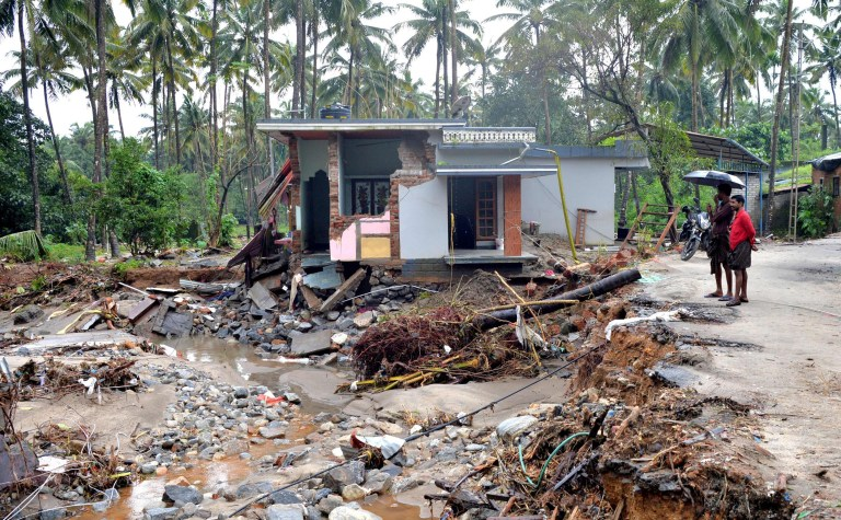 TOPSHOT - CORRECTION - Indian people look at a houses destroyed by a landslide at Kannapanakundu village, about 422 km north of Trivandrum, in the south Indian state of Kerala, on August 18, 2018. - Pressure intensified on August 18 to save thousands still trapped by devastating floods that have killed more than 300 in the Indian state of Kerala, triggering landslides and sending torrents sweeping through villages in the region's worst inundation crisis in a century. (Photo by MANJUNATH KIRAN / AFP) / Sending a quality repeat of this image. Please immediately remove the erroneous version from all your online services and delete it from your servers. If you have been authorized by AFP to distribute it to third parties, please ensure that the same actions are carried out by them. Failure to promptly comply with these instructions will entail liability on your part for any continued or post notification usage. Therefore we thank you very much for all your attention and prompt action. We are sorry for the inconvenience this notification may cause and remain at your disposal for any further information you may require.MANJUNATH KIRAN/AFP/Getty Images