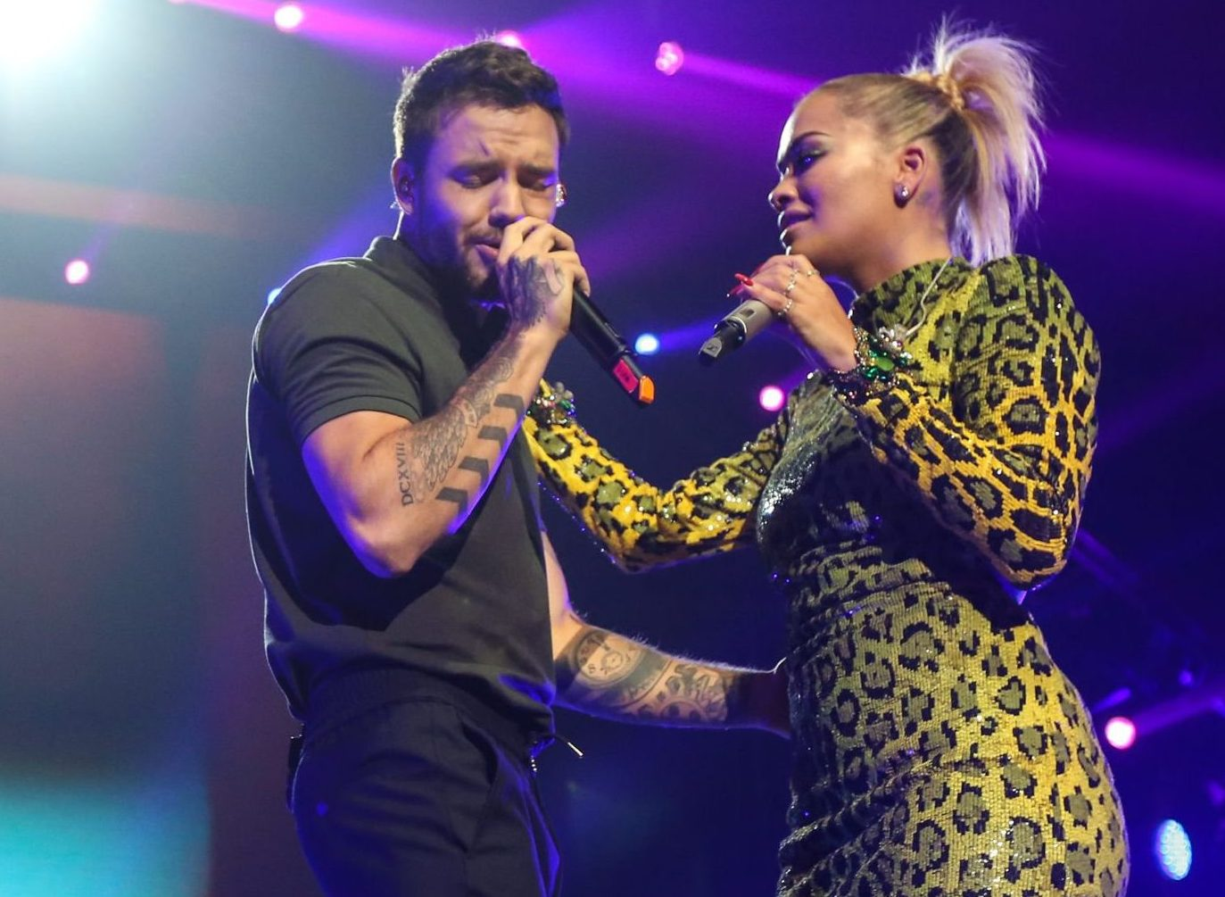 Liam Payne whispers into Rita Ora's ear while she 'grinds on him' off-stage at pre-VMAs concert