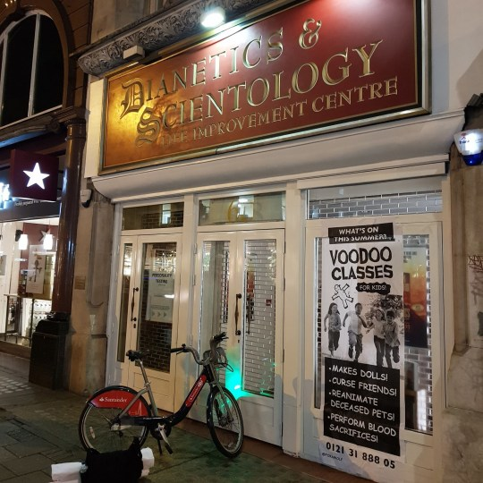 Caption 'Voodoo classes' poster plastered over Scientology shop picture: Foka Wolf METROGRAB https://www.facebook.com/fkawlf/photos/rpp.961113060607884/2171727776213067/?type=3&theater