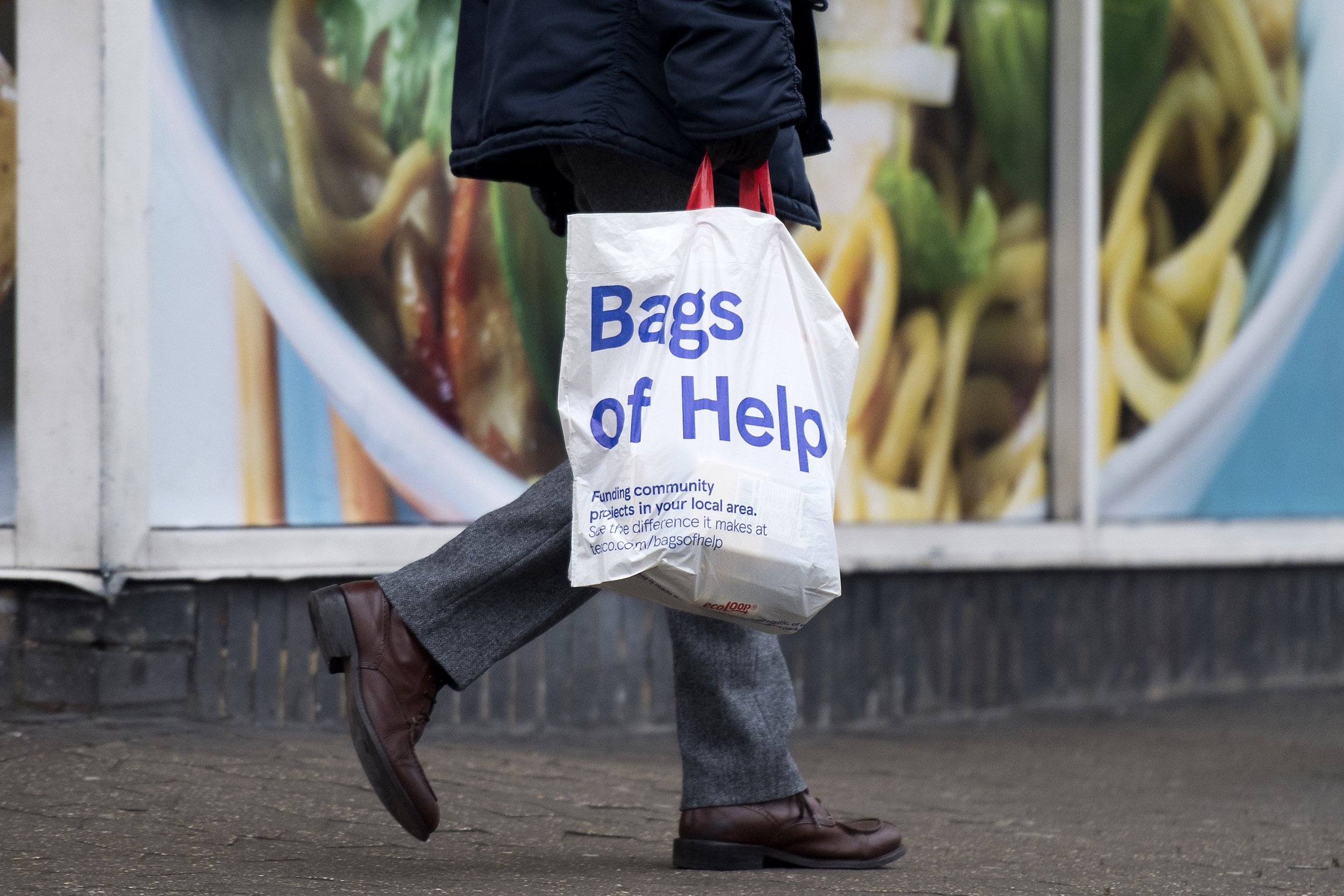 A man leaves with his goods in a plastic carrier bag after shopping at a branch of Tesco in south London, on January 9, 2018. / AFP PHOTO / Justin TALLIS (Photo credit should read JUSTIN TALLIS/AFP/Getty Images)