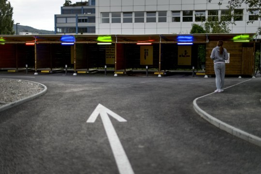 "A prostitute faces the so-called ""sex boxes"" at the opening day of Switzerland's first sex drive-in on August 26, 2013 in Zurich, which is aiming to get prostitution off the city streets. The drive-in, which as darkness began to fall was bathed in colourful lights, has a track where the sex workers can show off their assets and negotiate a price, and nine so-called ""sex boxes"" where they and their clients can park and conclude the transaction. AFP PHOTO / FABRICE COFFRINI (Photo credit should read FABRICE COFFRINI/AFP/Getty Images)"