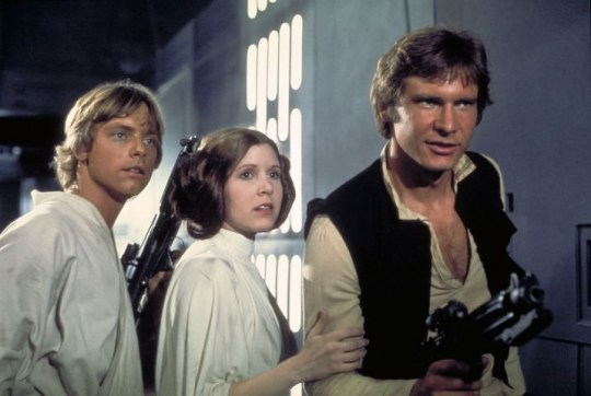 """Film, """"Star Wars: Episode IV, A New Hope"""" (1977) Actors, from left, Mark Hamill as Luke Skywalker, Carrie Fisher as Princess Leia and Harrison Ford as Han Solo, appear in a scene from Lucasfilm's """"Star Wars: Episode IV, A New Hope,"""" in this undated promotional photo. Lucasfilm Ltd. and 20th Century Fox announced Tuesday, Feb. 10, 2004, that the original three """"Star Wars"""" films will be released on DVD on Sept. 21, 2004, in North America. (AP Photo/Lucasfilm, Ltd. & TM)...A...ENT...USA"""
