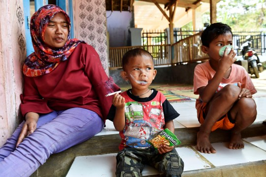 PIC FROMJefri Tarigon / Caters News - (PICTURED: Rafi Ananda Pamungkas, smoking next to his mum Maryati) - The chain-smoking toddler who whipped the internet into a frenzy could develop brain damage is he keeps up his shocking habit, experts have revealed. Rapi Ananda Pamungkas, two, was smoking two packs a day after becoming addicted by collecting used butts outside his mums stall in Sukabumi, Indonesia.SEE CATERS COPY