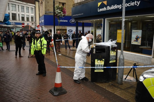 "A police forensics officer looks for evidence inside a cordon in Peel Square, following a stabbing incident in the centre of Barnsley, northern England on September 8, 2018. - Police made an arrest on Saturday following a ""serious incident"" in the northern English city of Barnsley that left one man with stab injuries. Traders at a local covered market said they and parts of the town centre were locked down over the incident, sparked by reports of an individual with a knife. (Photo by Oli SCARFF / AFP)OLI SCARFF/AFP/Getty Images"