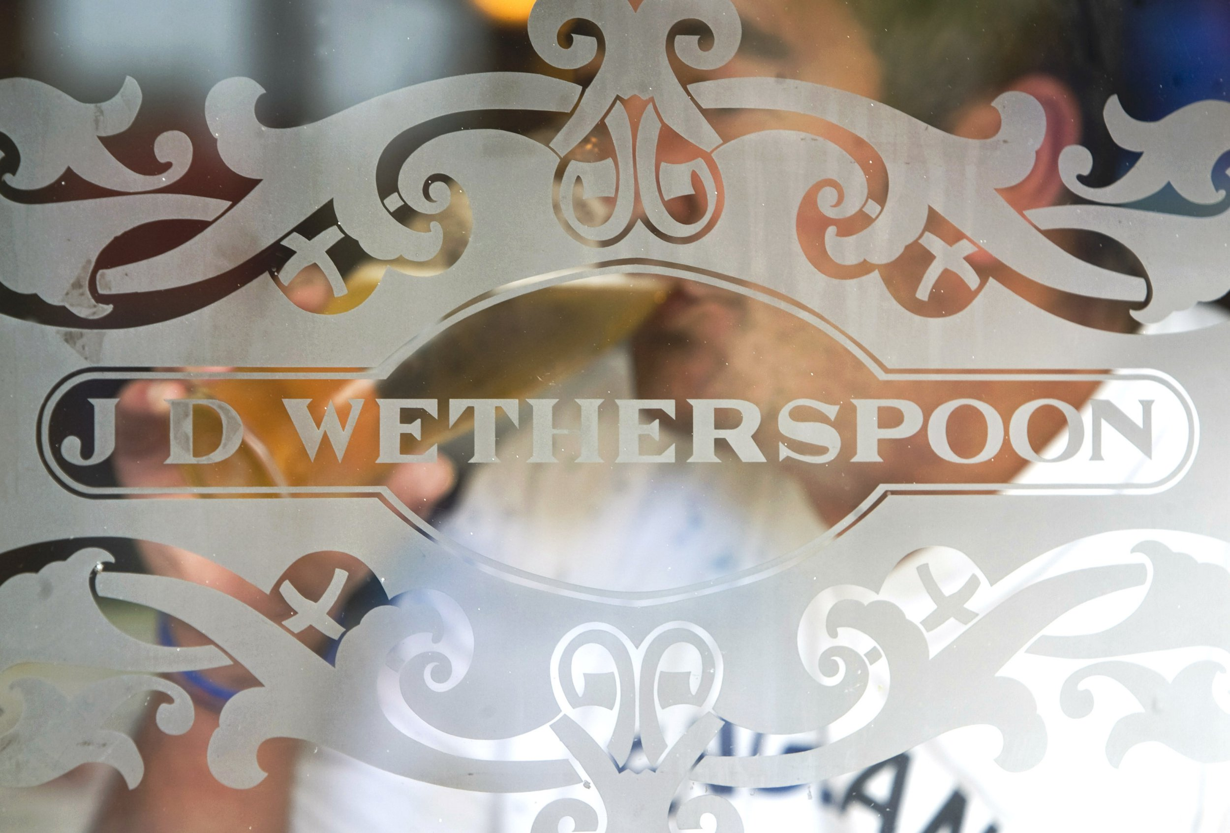 UNITED KINGDOM - SEPTEMBER 09: The J.D. Wetherspoon logo is displayed on a glass door at a pub in Hornchurch, U.K., on Wednesday, Sept. 9, 2009. Britain's branded pub chains from Wetherspoons to Marston's are expanding during the U.K.'s worst recession since World War II, offering bargain beers and food as individual pubs go out of business. (Photo by Chris Ratcliffe/Bloomberg via Getty Images)