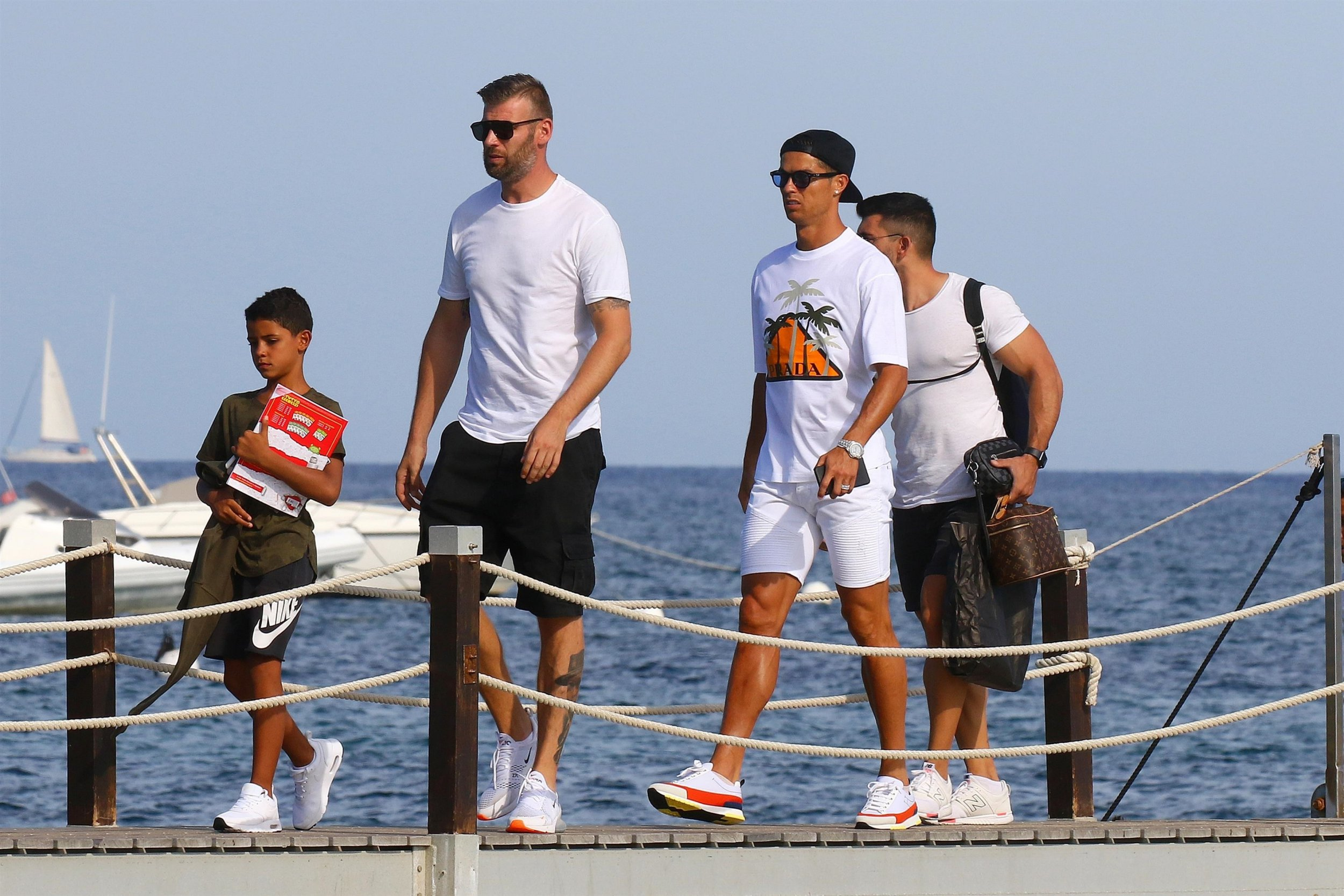 BGUK_1332886 - ** RIGHTS: ONLY UNITED KINGDOM ** Saint Tropez, FRANCE - Portuguese professional footballer Cristiano Ronaldo pictured on holiday in St Tropez, France with his son and girlfriend Georgina Rodriguez. Cristiano wore a white Prada graphic t-shirt with white shorts, white trainers, baseball cap and sunglasses. Georgina wore a leopard print dress with sandals. Pictured: Cristiano Ronaldo BACKGRID UK 10 SEPTEMBER 2018 UK: +44 208 344 2007 / uksales@backgrid.com USA: +1 310 798 9111 / usasales@backgrid.com *UK Clients - Pictures Containing Children Please Pixelate Face Prior To Publication*