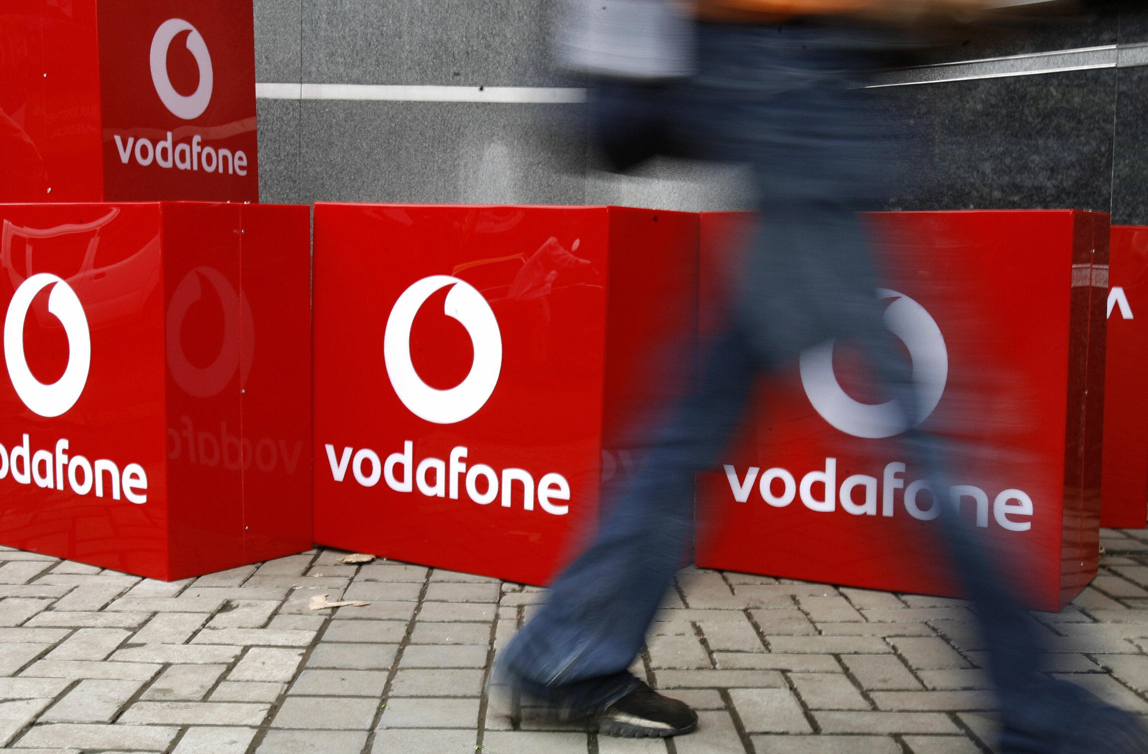 """An Indian man walks past the signboard of telecom firm """"Vodafone"""" outside the corporate office in India's financial capital Mumbai, 20 September 2007. Vodafone purchased Hutchison Essar India in March 2007 for 11.1-billion USD. The re-branding marks the completion of UK-based Vodafone's acquisiton of Hong Kong-based Hutchison Telecommunication Limited's Indian assets in May 2007. The Indian unit's formal name is Vodafone Essar as the other partner is Indian steel-to-shipping conglomerate Essar. AFP PHOTO/ Sajjad HUSSAIN (Photo credit should read SAJJAD HUSSAIN/AFP/Getty Images)"""