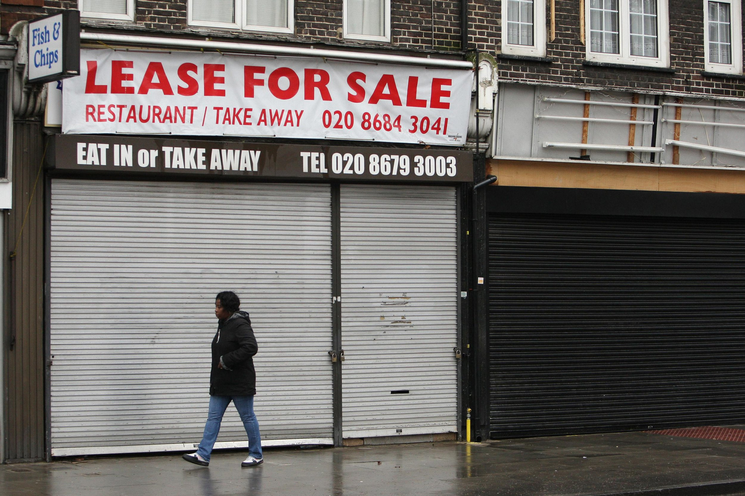 A woman walks past shuttered shops on Streatham High Road in south London. Official figures today reveal the UK is officially in recession. The economy saw its worst output performance since 1980 in the final three months of 2008.