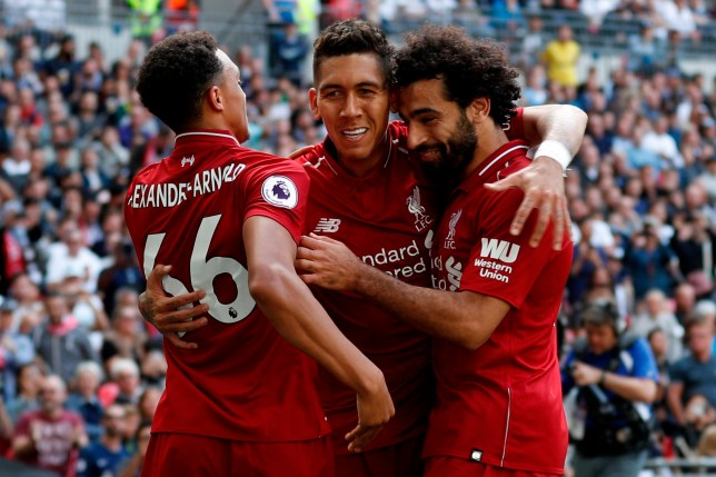 TOPSHOT - Liverpool's Brazilian midfielder Roberto Firmino (C) celebrates after scoring their second goal with Liverpool's English defender Trent Alexander-Arnold (L) and Liverpool's Egyptian midfielder Mohamed Salah during the English Premier League football match between Tottenham Hotspur and Liverpool at Wembley Stadium in London, on September 15, 2018. Liverpool won the game 2-1. (Photo by Adrian DENNIS / AFP) / RESTRICTED TO EDITORIAL USE. No use with unauthorized audio, video, data, fixture lists, club/league logos or 'live' services. Online in-match use limited to 120 images. An additional 40 images may be used in extra time. No video emulation. Social media in-match use limited to 120 images. An additional 40 images may be used in extra time. No use in betting publications, games or single club/league/player publications. / ADRIAN DENNIS/AFP/Getty Images