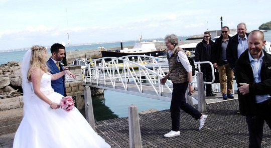 """A newly married couple were stunned when Prime Minister Theresa May 'crashed' their waterside wedding. Jason and Michelle Dight, had just exchanged their vows at the yacht haven in Cowes, Isle of Wight, and were having photos taken in the marina when Mrs May, flanked by security, turned-up by boat at the Royal Yacht Squadron. She then posed for pictures with the amazed couple before continuing to the town centre. An astounded Michelle, 32, said: """"We decided to pose for photos near the jetty. We saw this great big motor cruiser. It pulled up at the jetty and someone said 'It's Theresa May.' SEE OUR COPY FOR DETAILS. Please byline: Glass House Productions/Solent News ? Glass House Productions/Solent News & Photo Agency UK +44 (0) 2380 458800"""