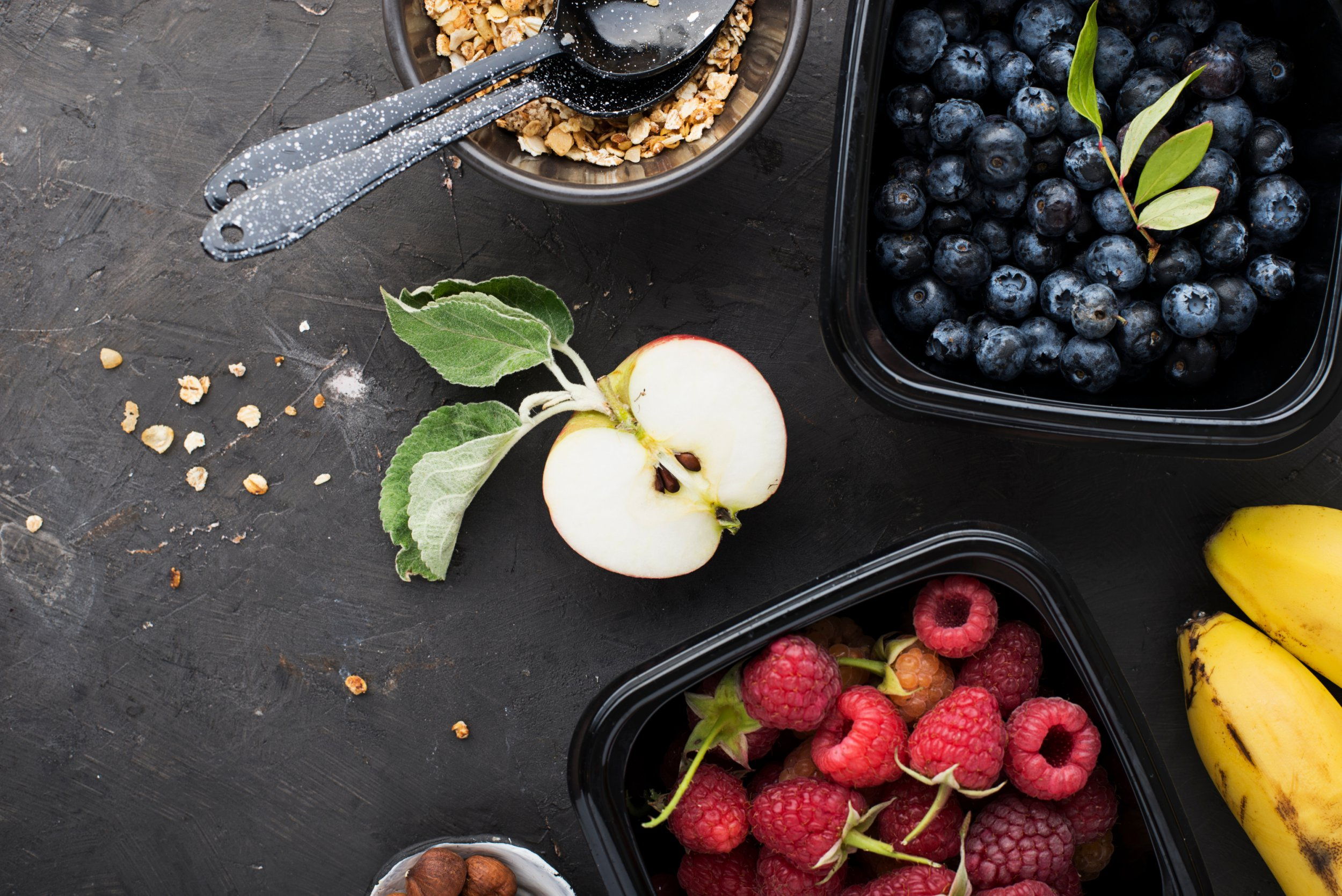 Black plastic containers take-away for a healthy snack food with raspberries, blueberries. Ingredients of healthy breakfast: granola, oat flakes, berries, nuts, apples, bananas. Top View; Shutterstock ID 1162363981; Purchase Order: -