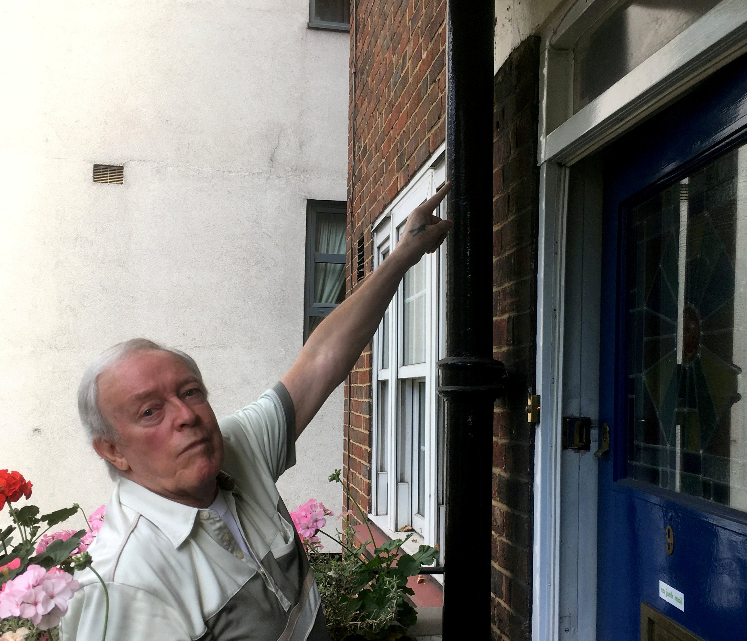 Len James points to the spot where he had installed a CCTV camera outside his flat. See National News story NNCAMERA; A pensioner who put CCTV cameras on his flat to reduce crime was prosecuted by his council who ordered him to remove them because they breached his tenancy agreement and damaged the brickwork. Len James, 77, was left with a ?2,000 costs order, but said his pair of cameras helped catch robbers, car vandals and bike thieves after he installed them in his south London block of flats. The retired plumber and heating engineer said they also kept drug dealers away as they overlooked the rear and front from his second-storey flat in Battersea. But he was ordered to pay court costs to his council after it got a county court order to have them removed because they breached a ban in his tenancy agreement to alter the outside of the property.