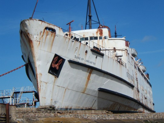 An old abandoned ocean liner is set to be brought back to life - by ZOMBIES. The spooky cruise liner started out as a passenger ferry but has been lying lifeless and empty since the mid-1980s. It is now going to open its doors to the walking dead thanks to company Zombie Infection. Pictured is The Duke of Lancaster ship which is permantly moored in the Dee Estuary in North Wales before being graffitied and turned into a zombi ship. ? WALES NEWS SERVICE