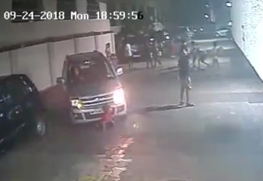 This is the moment that a boy miraculously survived being run over by a car - and went straight back to playing football. See SWNS story SWSHOELACE; The shocking incident occurred at Kamraj Nagar in Mumbai, India, on September 24 and was caught on a CCTV camera. The footage shows a group of children playing on an empty road. One of them in a red t-shirt sits down to tie his shoe lace. At the same time a driver moves her car from the parking slot and passes over the boy after failing to spot him in the dim street light.