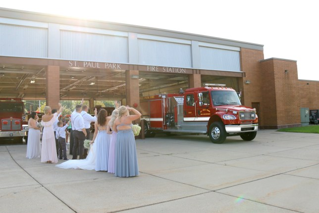 Friends and family of Jeremy Bourasa, 39, and Krista Bourasa, 32, wave at a fire engine on their wedding day. Mr. Bourasa had to leave his own wedding to attend a fire a volunteer firefighter - and his new wife couldn?t be more PROUD. St. Paul Park, Minnesota, USA. See story NYFIRE .A hero firefighter left his own wedding to go and fight a blaze and returned three hours later - just in time for his first dance. Dad-of-two Jeremy Bourasa, 39, had just tied the knot to bride Krista Boland, 32, when the call came in that a house was burning down. The volunteer fireman, who was posing for official photos with his new wife at the time, dropped everything and changed into his uniform. He then ran outside of the venue - which was, conveniently, the fire station where he is based - and jumped into the same fire truck Krista had arrived in a few hours earlier.