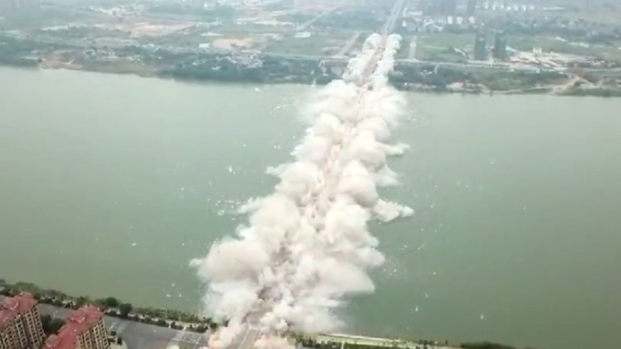 Pic shows: The moment of bridge demolition Thousands watched as engineers blew up a 5,000-foot bridge which has become obsolete due to population demands after just 23 years of use. The busy multi-lane bridge spanning the Gan River - known in Chinese as ???Ganjiang??? - was sealed off and residents asked to steer clear as demolition works took place at precisely 10:18am on 28th September. The Ji'an Ganjiang Bridge, in East China's Jiangxi province, was rigged with several tonnes of explosives on its four main columns and 61 piers. All 1,577 metres (5,173 feet) of the bridge, which was roughly 50 feet wide, was to be brought down simultaneously into the waters of the Gan River. Witnesses recorded spectacular footage of the countdown and the explosion that followed, with videos showing TNT blowing up at the same time all along the bridge. Residents were standing so far away that the cloud of smoke and debris was spotted first before sound waves from the blast reached their ears, the video shows. The 23-year-old bridge, for which officials approved the demolition job in June, was brought down in a matter of seconds. Construction for the Ji'an Ganjiang Bridge began on 23rd September 1993 and opened to traffic on 16th December 1995. It will make way for a taller, wider bridge, which will better serve a Ji'an population currently standing at 4.8 million inhabitants, 530,000 of whom live in the metropolitan areas. Work for the new bridge will begin in January next year and is expected to open to traffic in June 2021.