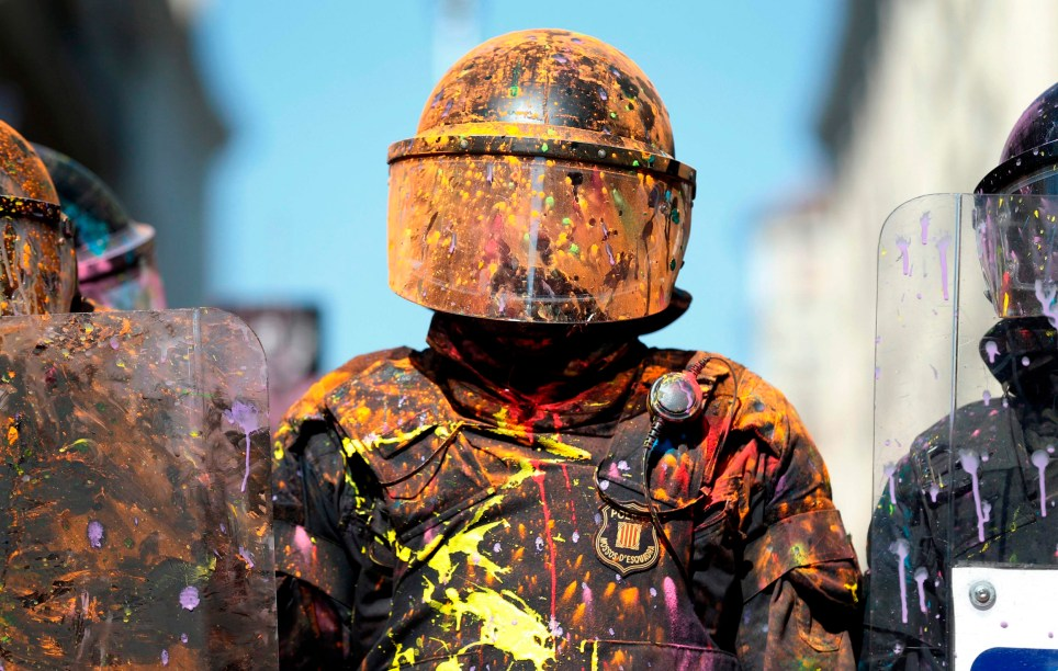 Catalan regional police 'Mossos D'Esquadra' officers covered in paint stand guard after clashing with separatist protesters during a counter-protest against a demonstration in support of Spanish police in Barcelona on September 29, 2018. - Monday, October 1, will mark one year since a banned independence referendum in Catalonia which was met with a massive police crackdown, captured the world's attention and plunged Spain into its worst political crisis in decades. (Photo by Pau Barrena / AFP)PAU BARRENA/AFP/Getty Images