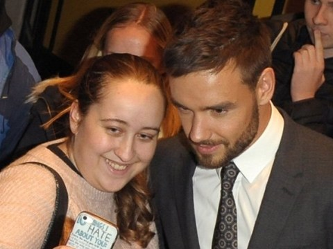 Liam Payne shows Cheryl what she's missing as he poses with fans in suit and tie