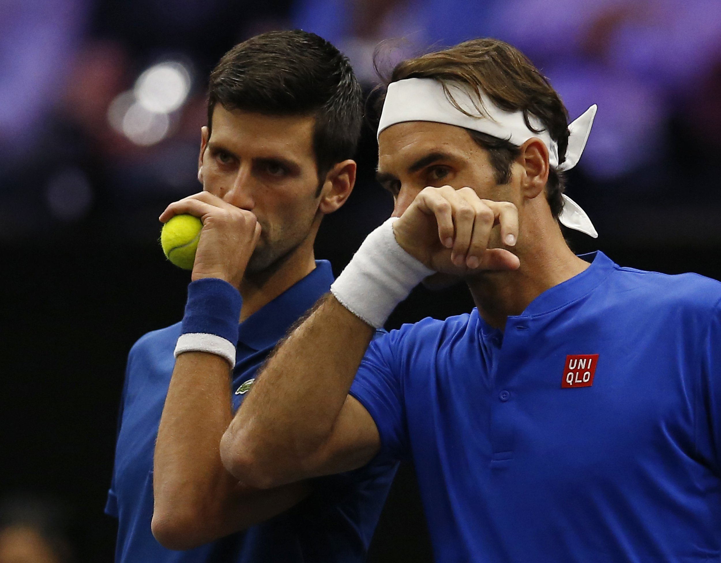 Team Europe's Roger Federer, right, whispers to Novak Djokovic during a men's doubles tennis match against Team World's Jack Sock and Kevin Anderson at the Laver Cup, Friday, Sept. 21, 2018, in Chicago. (AP Photo/Jim Young)