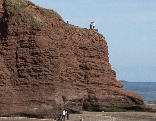 "PIC: APEX 01/10/2018 A man has been slammed after being pictured swinging a tot in his arms just inches from the edge of a perilous 100 foot sheer cliff. The heart in mouth scenes involving a man in white tee shirt and shorts were snapped at Dawlish Warren, Devon, on Saturday The man can be seen lifting the four or five year-old boy and dangling him by his arms above a potentially fatal plunge to the beach below. At one point the boy appears to recoil in terror and struggles to release himself from the man's grasp. The man then lifts him up again before walking off with a woman who was standing by during the whole shocking incident. Eyewitness Ian Wilmott, 39, was stunned by the scene. He said: ""I noticed the family approaching the far end of the cliffs and felt they were getting far too close to the edge. ""But when the man started swinging the young child over the edge I just couldn't believe what I was seeing. ""It looked like a crazily dangerous thing to do."" The red sandstone cliffs along the stretch of coast between Dawlish and Sidmouth are susceptible to erosion and are notorious for landslips and cliff falls. SEE STORY BY APEX NEWS - 01392 823144 ---------------------------------------------------- APEX NEWS AND PICTURES NEWS DESK: 01392 823144 PICTURE DESK: 01392 823145"