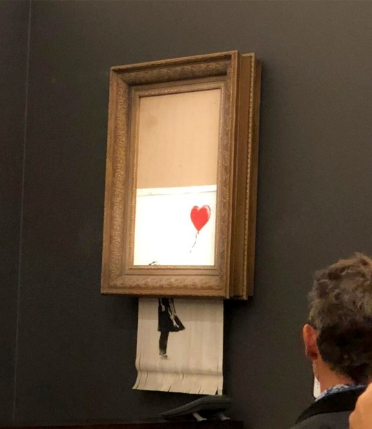 Handout photo issued by Sotheby's of Banksy's artwork, Girl With Balloon which shredded itself after being sold for more than ?1 million at auction. PRESS ASSOCIATION Photo. Issue date: Saturday October 6, 2018. The auction house was forced to admit it got ?Banksy-ed? after the canvas suddenly passed through a shredder installed in the frame. See PA story ARTS Banksy. Photo credit should read: Sotheby's/PA Wire NOTE TO EDITORS: This handout photo may only be used in for editorial reporting purposes for the contemporaneous illustration of events, things or the people in the image or facts mentioned in the caption. Reuse of the picture may require further permission from the copyright holder.
