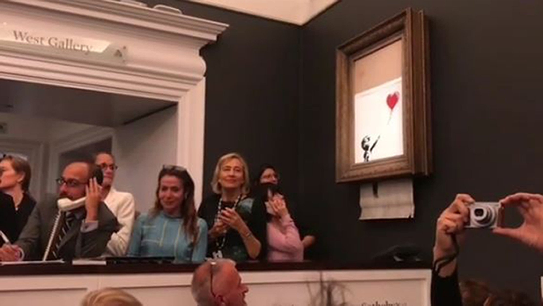 Undated screengrab from a video posted on Banky's instagram account showing the moment when the street artist's artwork, Girl With Balloon shredded itself after being sold for more than ?1 million at a Sotheby's auction. PRESS ASSOCIATION Photo. Issue date: Saturday October 6, 2018. See PA story ARTS Banksy. Photo credit should read: Banksy/PA Wire NOTE TO EDITORS: This handout photo may only be used in for editorial reporting purposes for the contemporaneous illustration of events, things or the people in the image or facts mentioned in the caption. Reuse of the picture may require further permission from the copyright holder.
