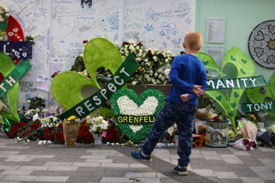 LONDON, ENGLAND - JUNE 14: A young boy looks at tributes left at a memorial wall by Grenfell Tower on the one year anniversary of the Grenfell Tower fire on June 14, 2018 in London, England. In one of Britain's worst urban tragedies since World War II, a devastating fire broke out in the 24-storey Grenfell Tower on June 14, 2017 where 72 people died from the blaze in the public housing building of North Kensington area of London. (Photo by Simon Dawson/Getty Images)