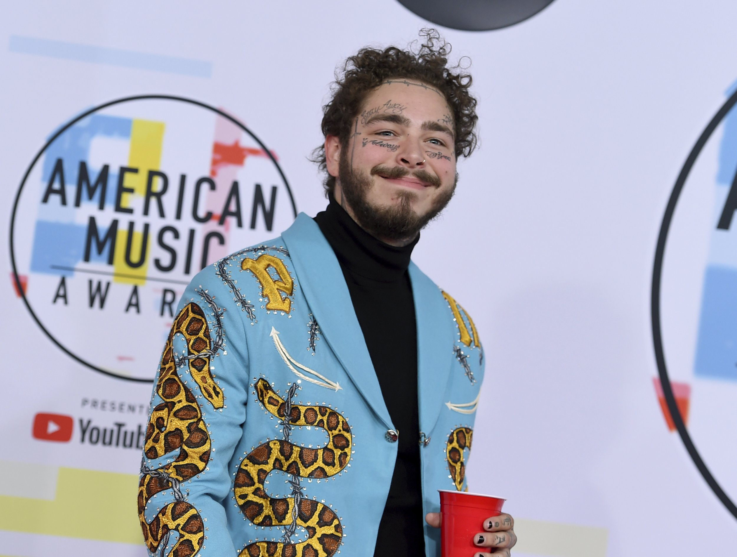 Post Malone is giving us life as he has a drink in his hand throughout entire AMAs