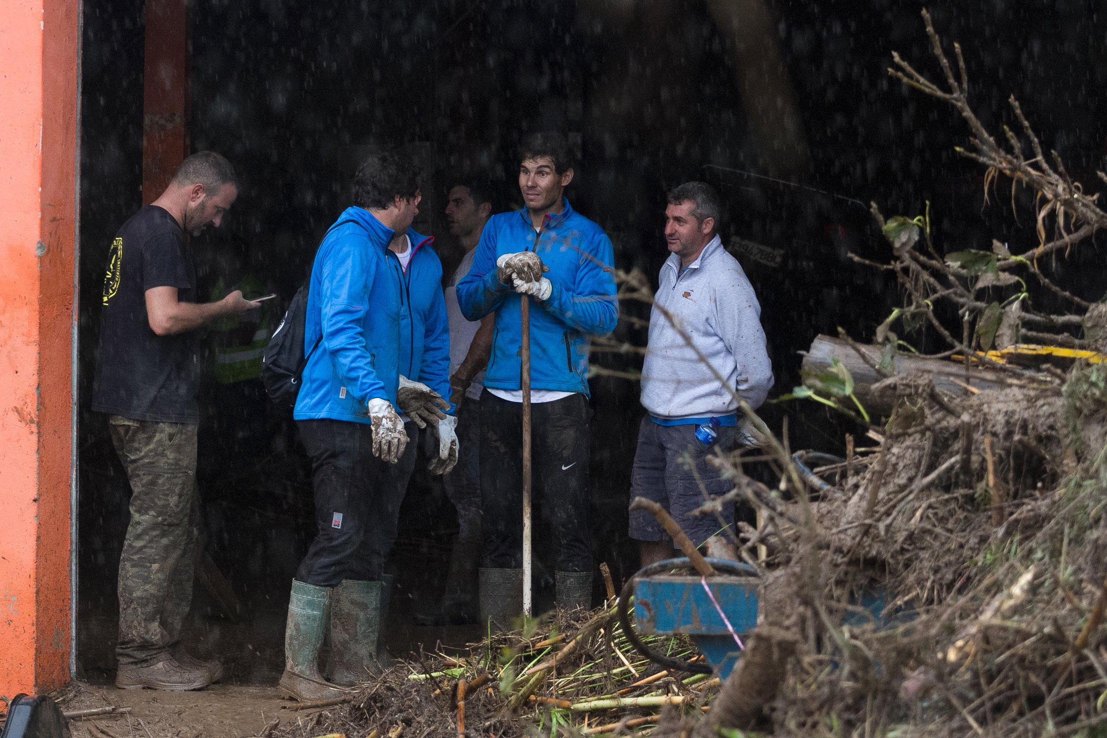 Spanish tennis player Rafael Nadal works with residents to clear the mud from their houses after flooding in Sant Llorenc, 60 kilometers (40 miles) east of Mallorca's capital, Palma, Spain, Wednesday, Oct. 10, 2018. Torrential rainstorms that caused flash flooding of water and mud on the Spanish island of Mallorca killed at least nine people, authorities said on Wednesday. (AP Photo/Francisco Ubilla)