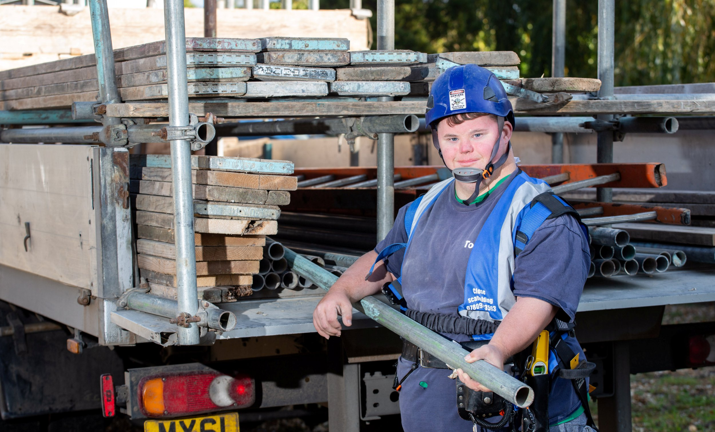"""Todd Scanlon, who has Down's syndrome works as a part-time scaffolder for Coles Scaffolding in Swindon. His boss Martyn Coles says he wants to see others with disabilities offered similar opportunities and is working to help Mr Scanlon, 29, get qualified. Swindon, Wiltshire. See SWNS story SWBRscaffold. A Down's Syndrome lad is living his 'dream' after a kind-hearted building firm took him on - as an apprentice scaffolder. Todd Scanlon, 29, has been employed on a permanent, part-time basis by Coles Scaffolding Contractors Ltd., working for them two full days-a-week. Todd had """"begged"""" scaffold company owner Martyn Coles, 35, for a job for the last two years. And Martyn, who has run the scaffolding company, based in Swindon, Wilts., for the last five years, has said Todd's disability is not holding him back. Todd loves his job, carrying out every task he is asked to do with focus and a smile, and cracking jokes with his colleagues."""