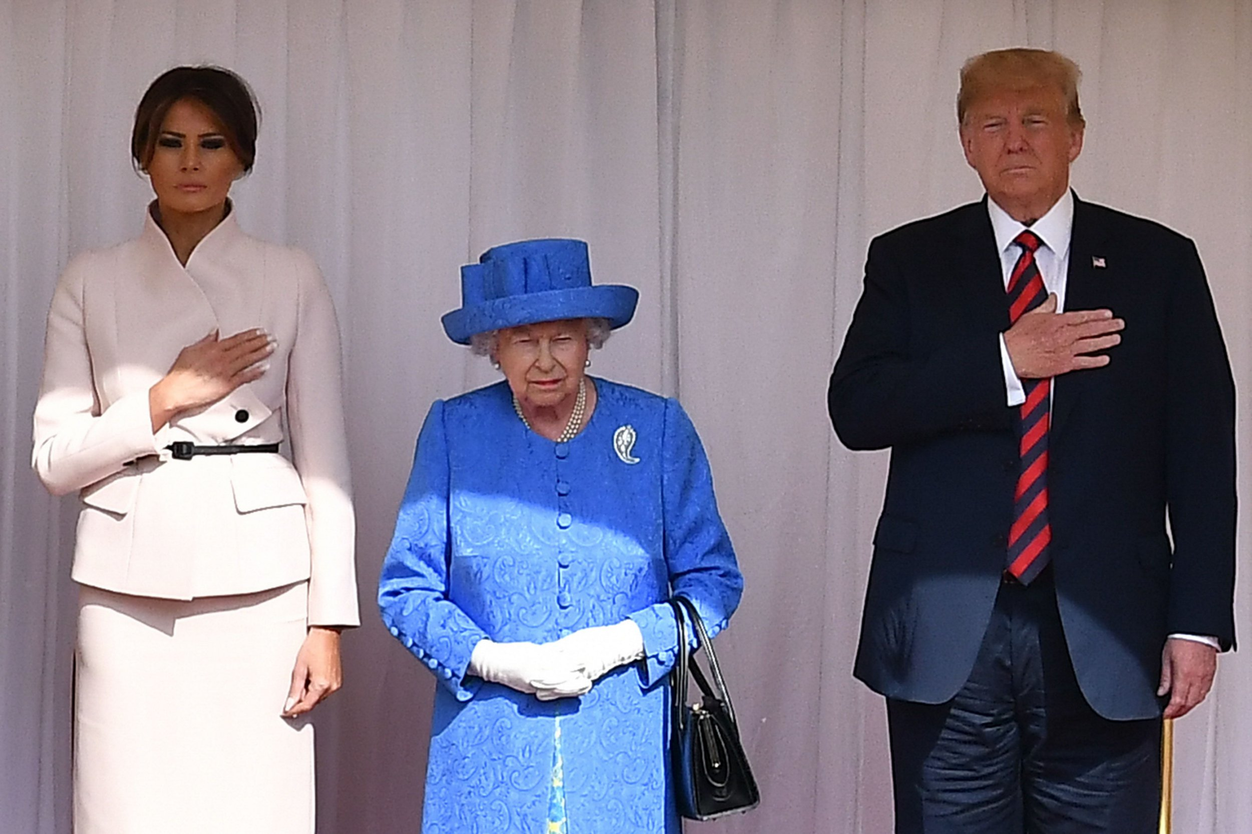 "Britain's Queen Elizabeth II (C) stands with US President Donald Trump (R) and US First Lady Melania Trump (L) on the dias in the Quadrangle listening to a band of guardsmen play the US national anthem during a ceremonial welcome at Windsor Castle in Windsor, west of London, on July 13, 2018 for an engagement with Britain's Queen Elizabeth II on the second day of Trump's UK visit. - US President Donald Trump launched an extraordinary attack on Prime Minister Theresa May's Brexit strategy, plunging the transatlantic ""special relationship"" to a new low as they prepared to meet Friday on the second day of his tumultuous trip to Britain. (Photo by Ben STANSALL / POOL / AFP) (Photo credit should read BEN STANSALL/AFP/Getty Images)"