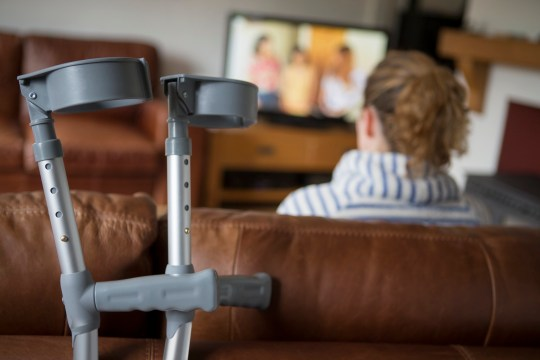 Crutches leaning on sofa with woman watching TV
