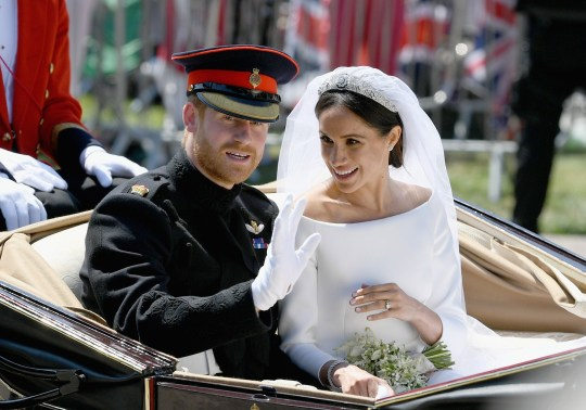 WINDSOR, ENGLAND - MAY 19: (L-R) Prince Harry, Duke of Sussex and Meghan, Duchess of Sussex leave Windsor Castle in the Ascot Landau carriage during a procession after getting married at St Georges Chapel on May 19, 2018 in Windsor, England. Prince Henry Charles Albert David of Wales marries Ms. Meghan Markle in a service at St George's Chapel inside the grounds of Windsor Castle. Among the guests were 2200 members of the public, the royal family and Ms. Markle's Mother Doria Ragland. (Photo by Jeff J Mitchell/Getty Images)