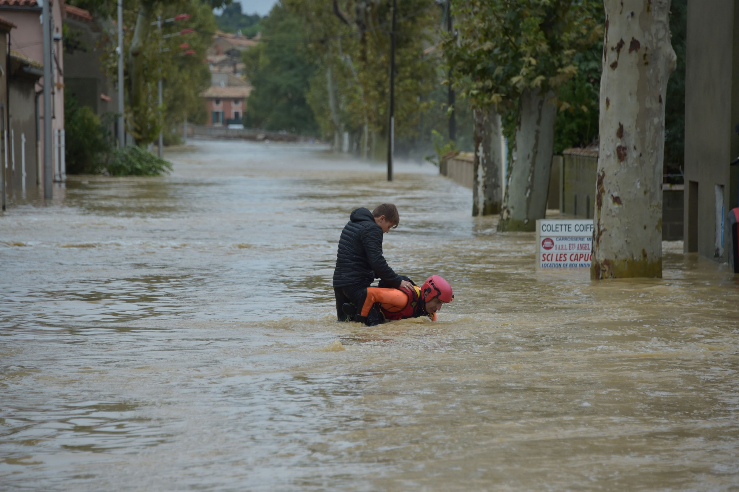 A firefighter helps a younster in a flooded street during rescue operation following heavy rains that saw rivers bursting banks on October 15, 2018 in Trebes, near Carcassone, southern France. - Six people died following storm and flash floods during the night of October 15 in the Aude department in southern France, authorities said. (Photo by Pascal PAVANI / AFP)PASCAL PAVANI/AFP/Getty Images