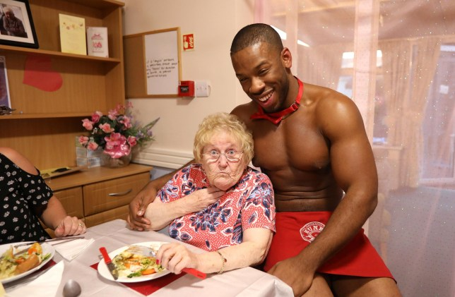 Butler in the buff with Peggy Rogers at Milton Care Lodge in Colchester, Essex. See SWNS copy SWCAbutlers: A group of elderly female residents at a retirement home have been served some cheeky dinners - after 'butlers in the buff' came to visit them. The care home granted the wish of their elderly residents and hired a group of scantily clad butlers, who served the ladies up a three-course meal. There were 23 guests in total with 11 of them being residents at the Milton Lodge retirement home at Colchester, Essex.