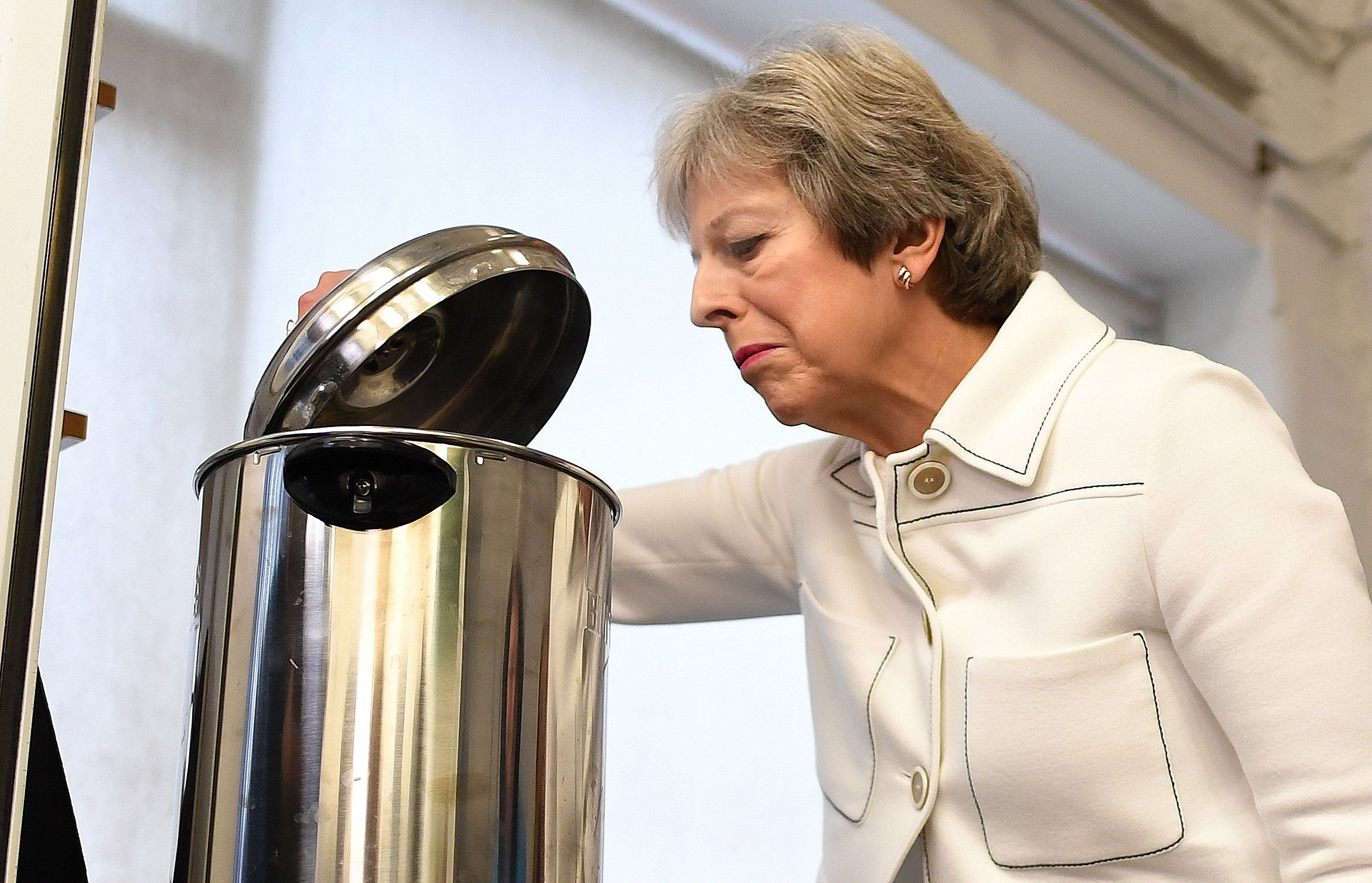 TOPSHOT - Britain's Prime Minister Theresa May peers into a hot water urn as she helps make drinks during a visit to social group in Vauxhall, south London, on October 15, 2018, where she launched the government's loneliness strategy. (Photo by Stefan Rousseau / POOL / AFP)STEFAN ROUSSEAU/AFP/Getty Images