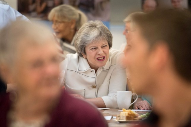 TOPSHOT - Britain's Prime Minister Theresa May reacts as she talks with people attending a social group in Vauxhall, south London, on October 15, 2018, where she launched the government's loneliness strategy. (Photo by Stefan Rousseau / POOL / AFP)STEFAN ROUSSEAU/AFP/Getty Images