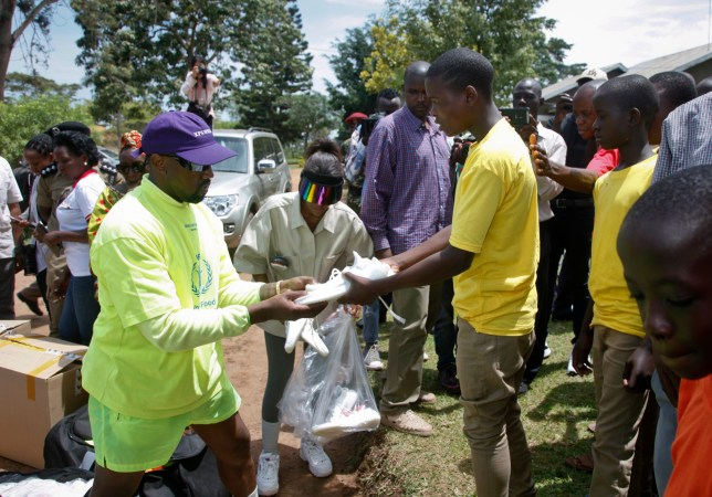the best attitude 6c44d fc150 Kanye West hands out Yeezys to Ugandan children as he and Kim Kardashian  tour Africa