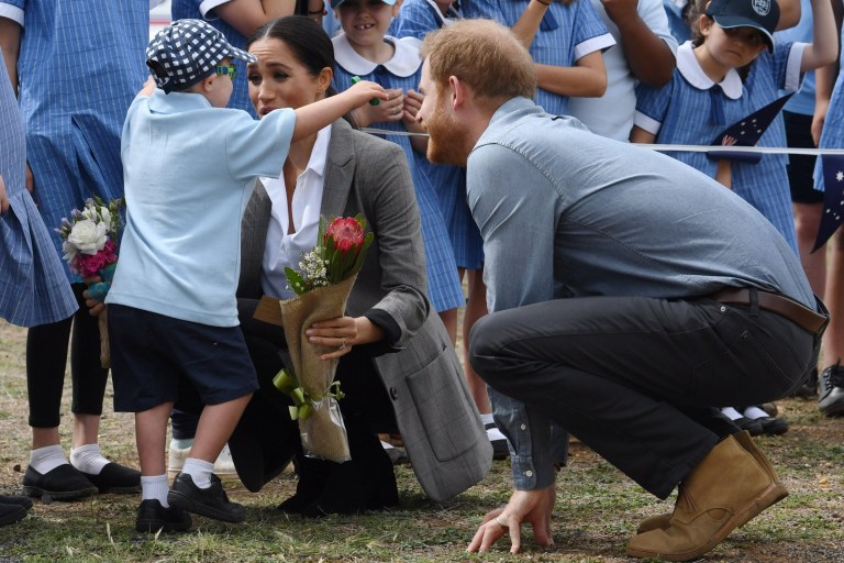 AAP via Press Association Images. Britain's Prince Harry, the Duke of Sussex looks on as his wife Meghan, the Duchess of Sussex is hugged by student Luke Vincent of Buninyong Public School following their arrival at Dubbo Regional Airport in Dubbo, Australia, Tuesday, October 17, 2018. The Duke and Duchess of Sussex are on a 3-week tour of Australia, New Zealand, Tonga, and Fiji and are in Sydney to launch the 2018 Invictus Games, an Olympic-style event for disabled and ill service people. (AAP Image/Dean Lewins)