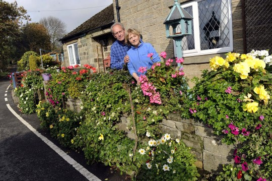 Pictured are Sally and Brian Williams outside their cottege on Hollin House Lane,Loxley Valley,who are in dispute with Sheffield City Council over their flower beds after a neighbour complained. See SWNS story SWLEflowers; Couple from Sheffield told to remove a bed of flowers they have tended to for three decades because the shrubs are a ???danger??? to road users