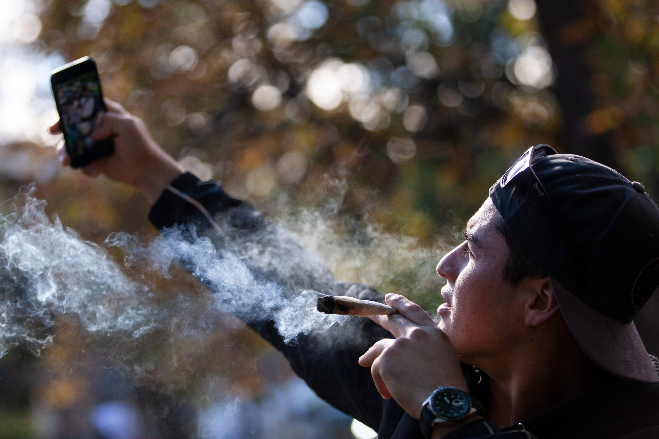 A man takes a selfie as he smokes a marijuana cigarette during a legalization party at Trinity Bellwoods Park in Toronto, Ontario, October 17, 2018. - Nearly a century of marijuana prohibition came to an end Wednesday as Canada became the first major Western nation to legalize and regulate its sale and recreational use. Scores of customers braved the cold for hours outside Tweed, a pot boutique in St John's, Newfoundland that opened briefly at midnight, to buy their first grams of legal cannabis.In total, Statistics Canada says 5.4 million Canadians will buy cannabis from legal dispensaries in 2018 -- about 15 percent of the population. Around 4.9 million already smoke. (Photo by Geoff Robins / AFP)GEOFF ROBINS/AFP/Getty Images