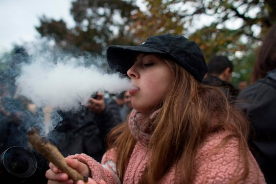 A woman smokes a marijuana cigarette during a legalization party at Trinity Bellwoods Park in Toronto, Ontario, October 17, 2018. - Nearly a century of marijuana prohibition came to an end Wednesday as Canada became the first major Western nation to legalize and regulate its sale and recreational use. Scores of customers braved the cold for hours outside Tweed, a pot boutique in St John's, Newfoundland that opened briefly at midnight, to buy their first grams of legal cannabis.In total, Statistics Canada says 5.4 million Canadians will buy cannabis from legal dispensaries in 2018 -- about 15 percent of the population. Around 4.9 million already smoke. (Photo by Geoff Robins / AFP)GEOFF ROBINS/AFP/Getty Images