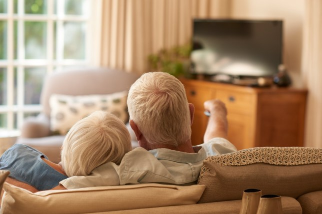 Rearview of an affectionate senior couple relaxing in each other's arms and watching television on a sofa in their living room at home; Shutterstock ID 614525708; Purchase Order: -