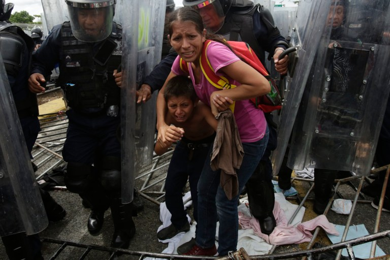A Honduran migrant mother and child are shielded by Mexican Federal Police from stones thrown by unidentified people, at the border crossing in Ciudad Hidalgo, Mexico, Friday, Oct. 19, 2018. The mother and child were unsuccessful in their attempt to cross into Mexico and were returned to the Guatemalan side. (AP Photo/Moises Castillo)