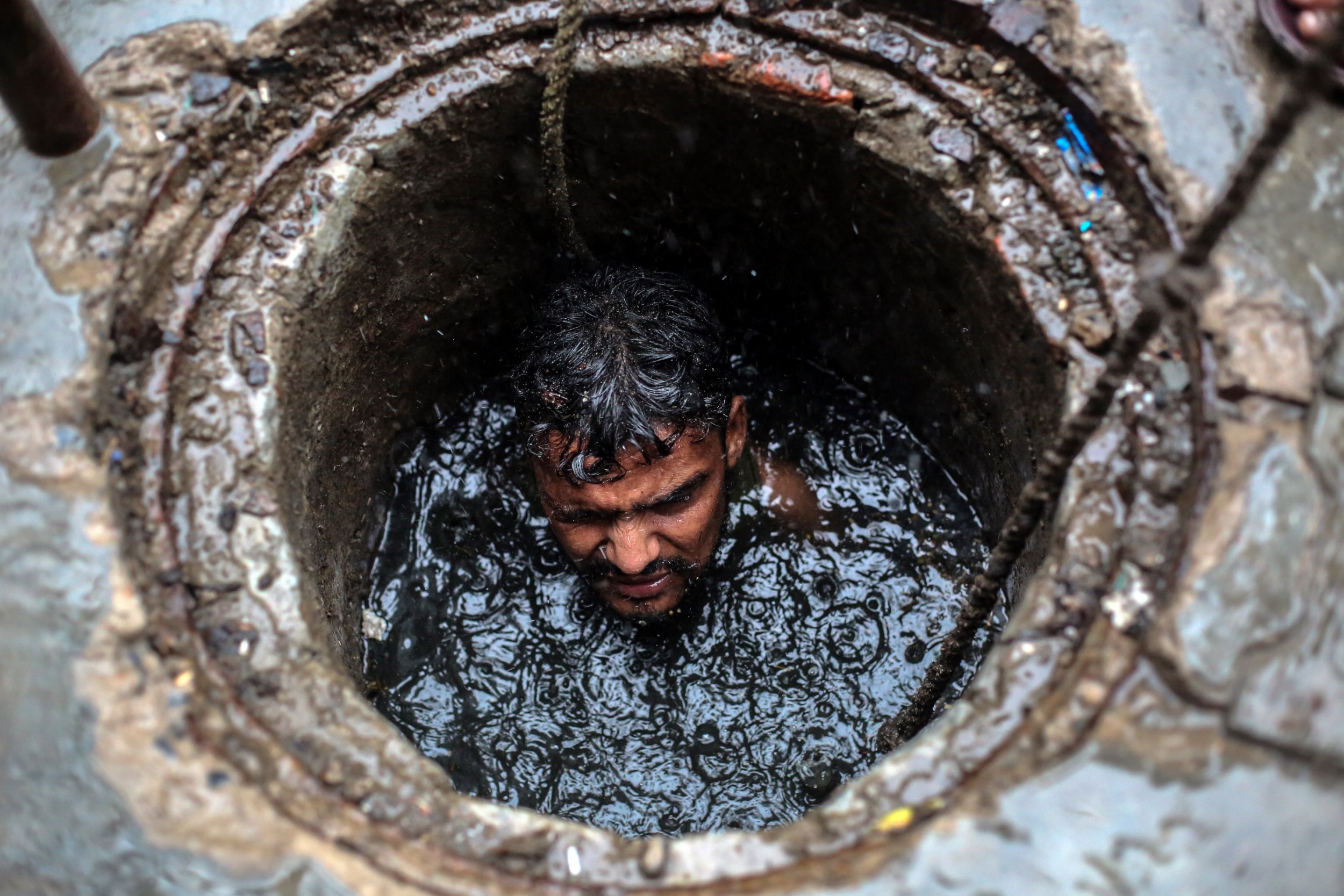 epa07110673 (03/26) Joney, a 26 year-old sewer worker cleans a sewer line in Ghaziabad, Uttar Pradesh, India, 26 July 2018. Joney along with other sewer workers cleans the sewer lines by going inside the pits in Ghaziabad area without any safety masks or any safety equipment except for a safety belt to lift them up. Recent official government statistics showed one manual scavengers has died every five days since the beginning of 2017 while cleaning sewers. This is one of the most dangerous jobs in India and its usually done by the Valmiki community, a sub-caste that is considered one of the lowest of the so-called ???untouchable??? or Dalit caste. Members of these communities have traditionally occupied cleaning and sanitation work in Indian society. EPA/RAJAT GUPTA ATTENTION: For the full PHOTO ESSAY text please see Advisory Notice epa07110670
