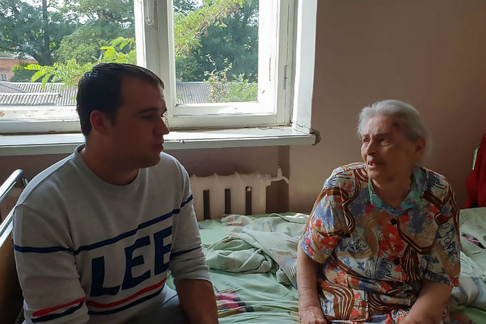 """Pic Shows: Leonid Shchepel (the man) and Klara Shalomovna; The man who saved an 88-year-old grandmother from a thug who had her pinned to the ground and broke her ribs has been fined by police for beating the attacker. Have-a-go hero Leonid Shchepel has been told be must pay 5,000 RUB (58 GBP) for beating up the thug who attacking Klara Melamed, 88. According to local media, Mrs Melamed suffered broken ribs and teeth during the attack in her hometown of Klintsy in the western Russian region of Bryansk Oblast. The incident was filmed by Shchepel on his smartphone and uploaded to social media. The unscrupulous attacker reported Shchepel to the police because of the beating he took and the hero has now been handed the fine. Shchepel said about the fine: """"I do not regret what I did. Klara's life and health are more important than the money."""" In the footage, Shchepel is hurrying along a footpath as a woman???s screams can be heard in the background. He quickly approaches a grassed area where a young man has the 88-year-old victim pinned to the ground as he pulls her hair and roughs her up. Shchepel does not hesitate and while filming himself in the act, he kicks the attacker in the head, sending him reeling and freeing the elderly victim. Still holding his phone in his hand to record the scenes, the have-a-go hero shouts at the young man and continues to kick him in the head. He says: """"Come on, fight with me, b*tch! Fight with me!"""" The humbled attacker remains on all-fours and does not attempt to fight back. He continues to take several hard blows to the face before Shchepel turns to the dishevelled old lady, who is covered in mud and looks scared out of her wits. The brave resident helps the granny to her feet and accompanies the woman across the road to her home. He turns back to the attacker, who is seen covering his head on all-fours on the ground. According to reports, Shchepel called an ambulance for the distressed old lady. She suffered two broken"""